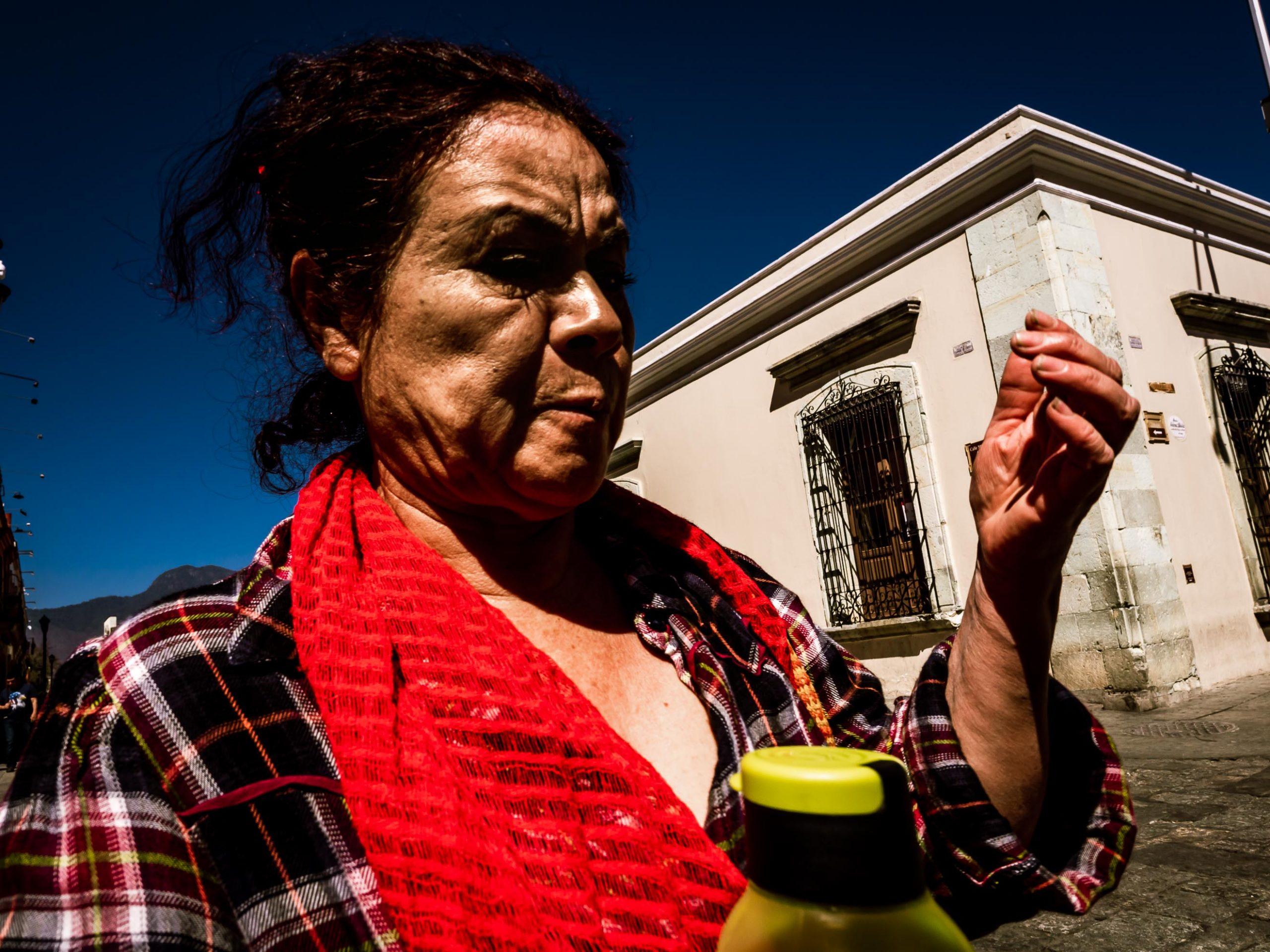 Frau im Zweifel an einer Straßenecke in Oaxaca, Mexiko