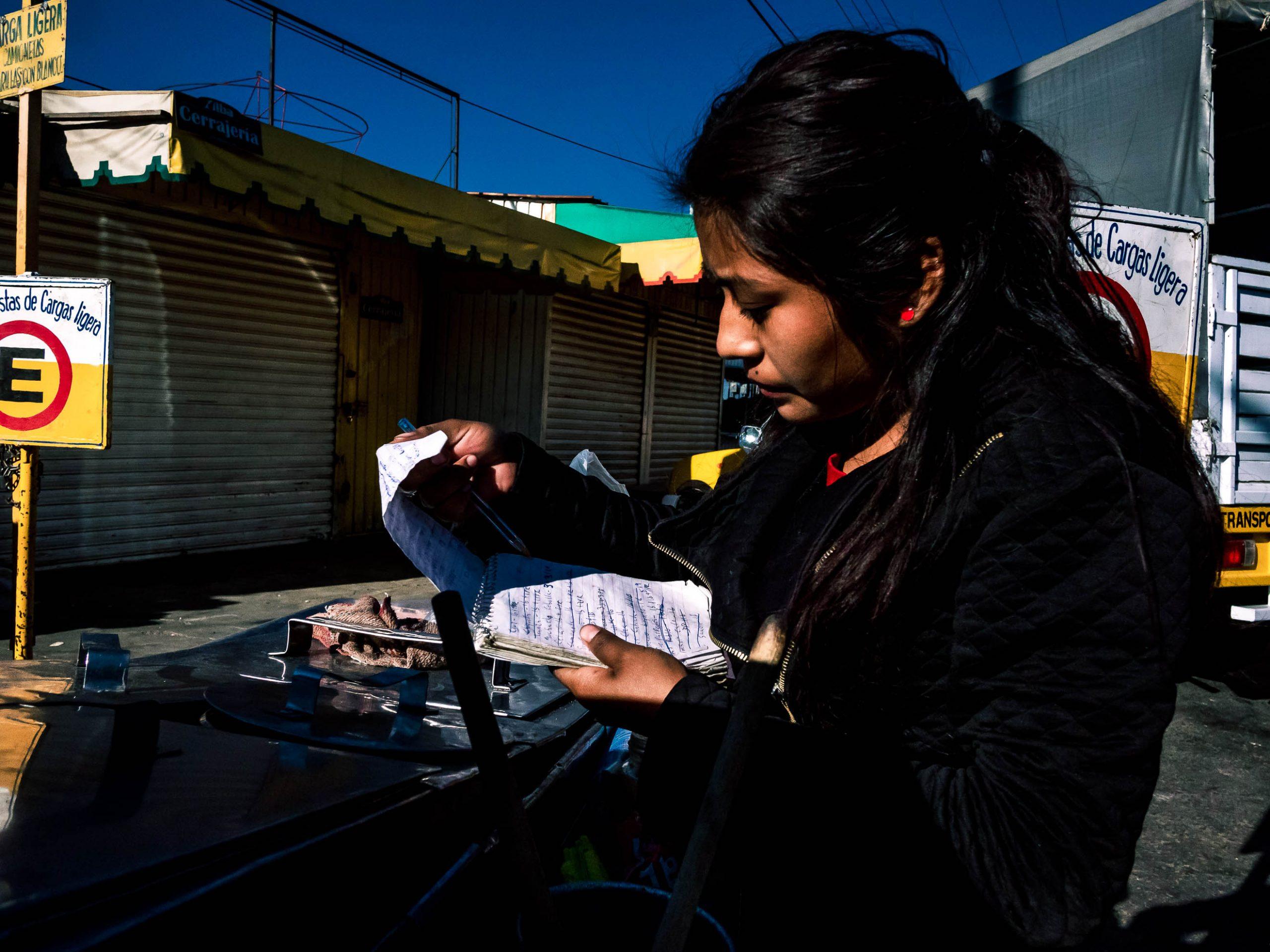Junge Frau addiert die Einnahmen auf Mercado de Abasto in Oaxaca Mexiko