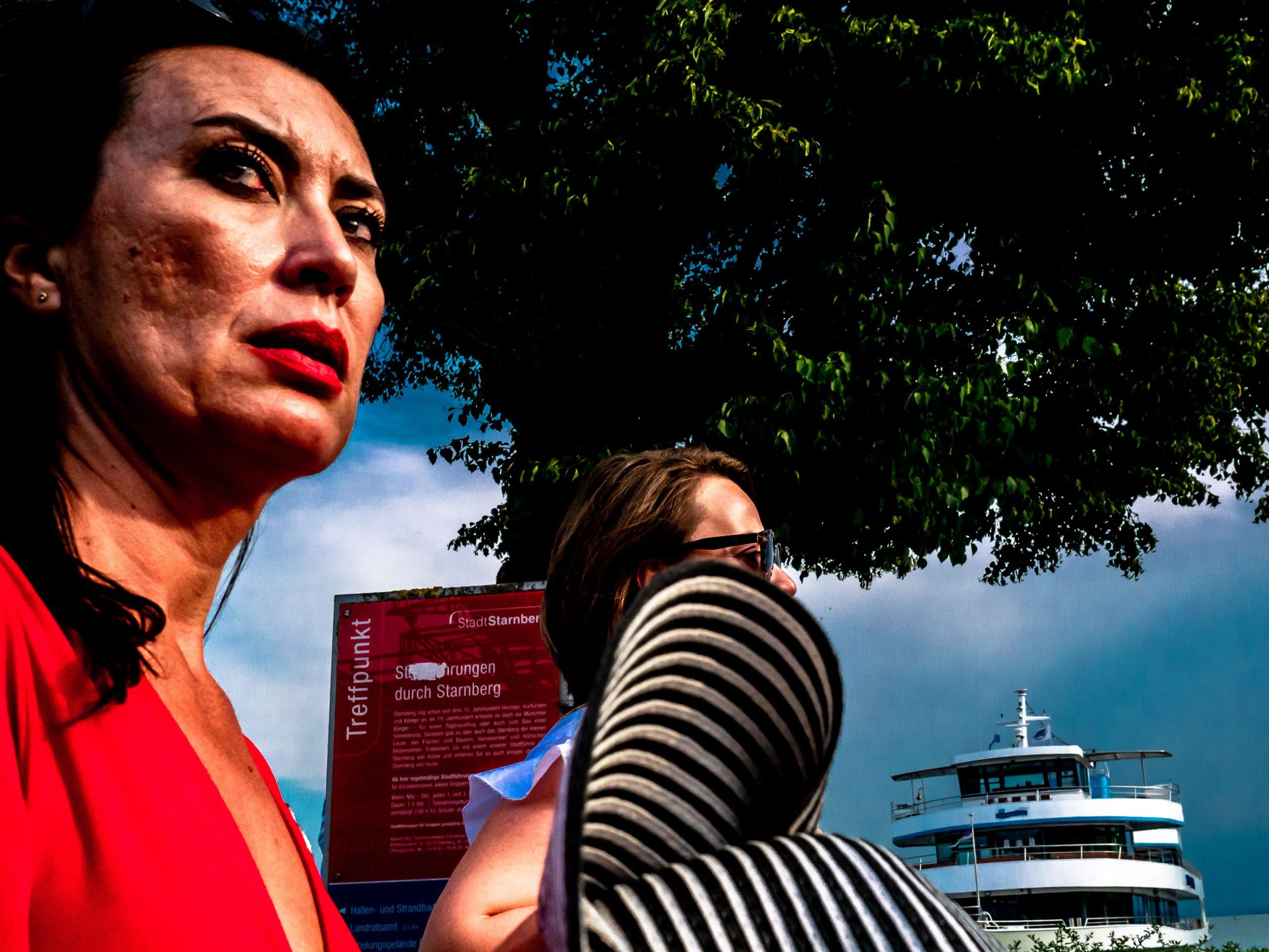 Frau schaut kritisch - Menschen auf der Strandpromenade in Starnberg am See in Bayern