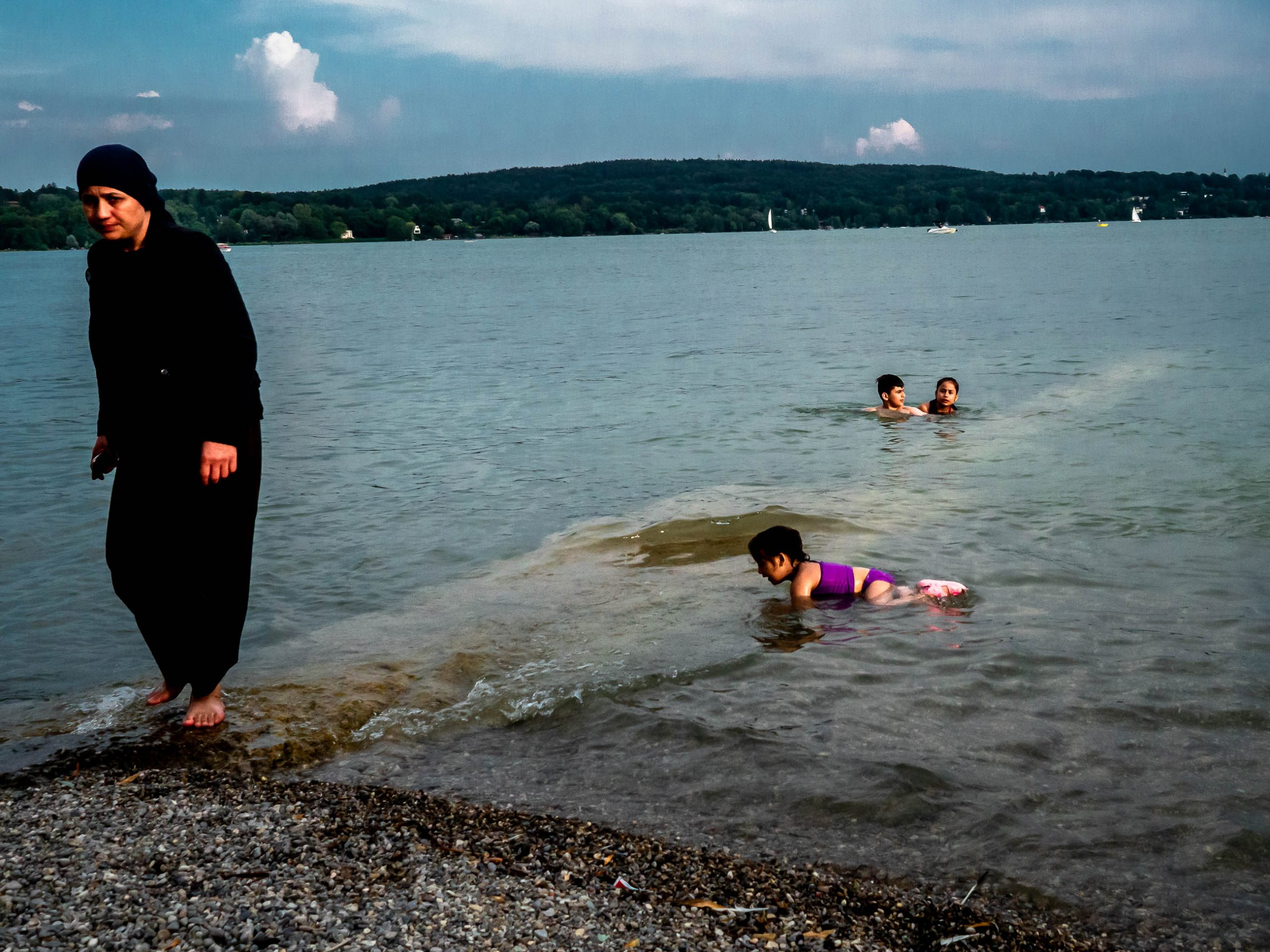 Arabian mother and her kids playing in the lake Starnberg in Bavaria, Germany