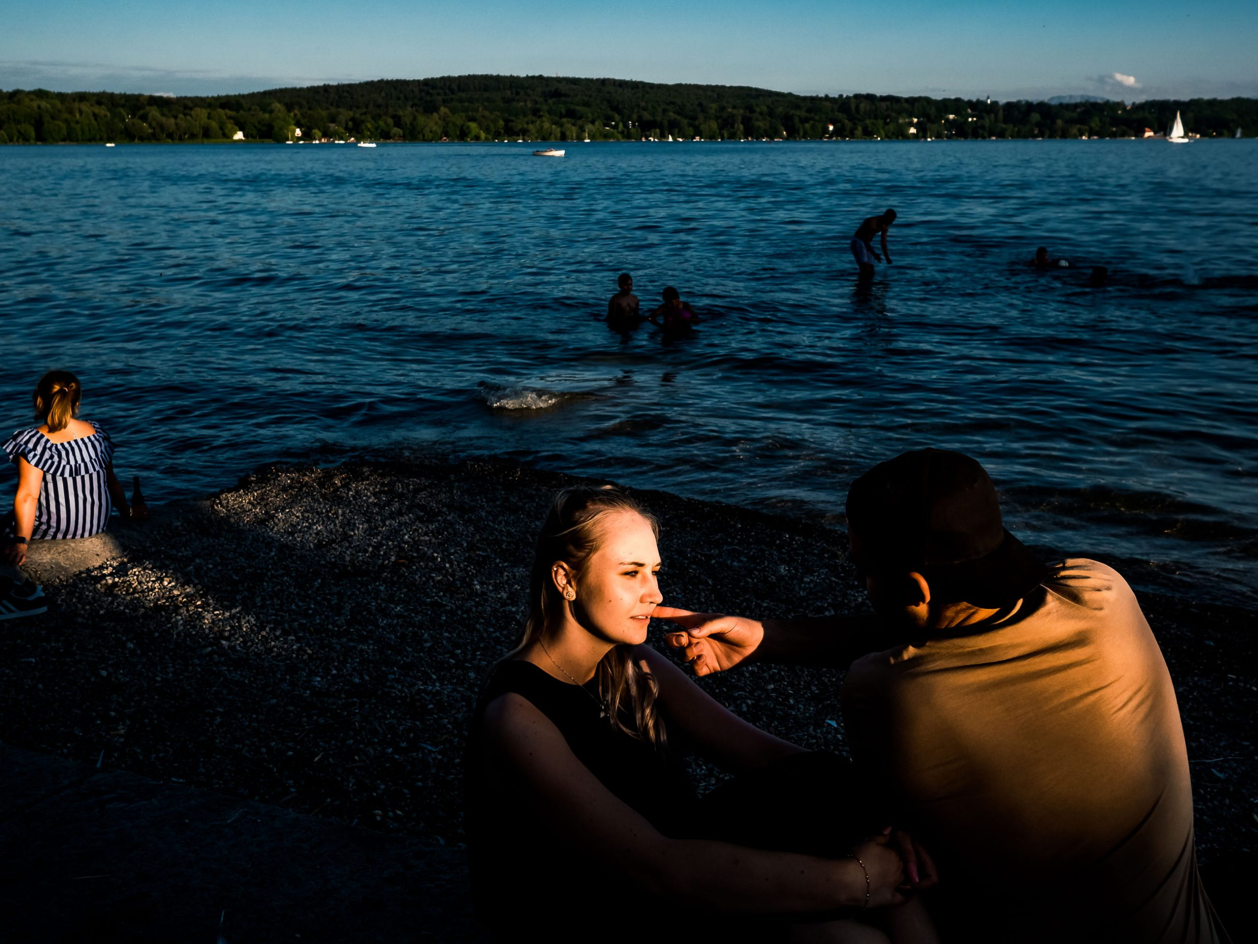 Couple in the evening sun talking at the Lake Starnberg in Bavaria, Germany
