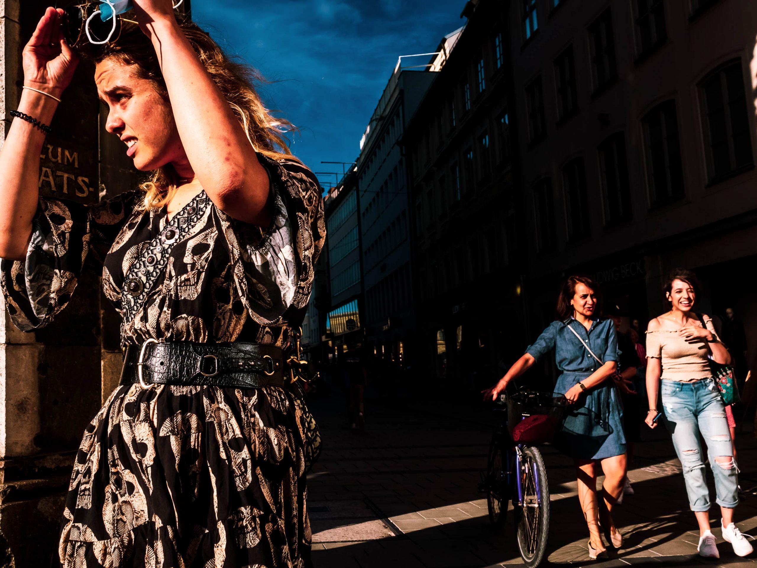 eine Frau biegt um die Ecke und zwei Passanten laufen gradaus weiter